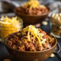 A brown bowl heaped with beef chili and garnished with cheddar cheese sits in front of a jar of cheese, crackers, and a second bowl of chili.