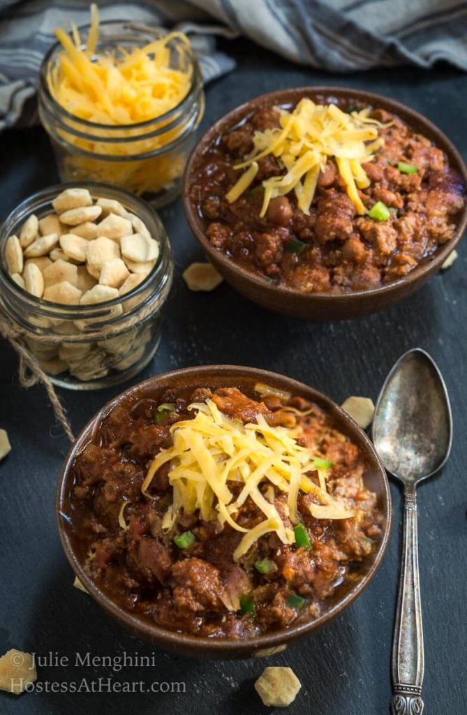 To down photo of two bowls of chili topped with shredded cheese in brown bowls next to small jars of cheese and soup crackers sitting on a slate tile.