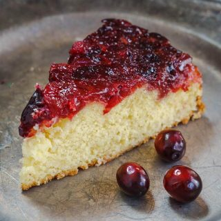 Cut piece of a Cranberry Upside-Down Cake on a metal plate with raw cranberries in the fore front.