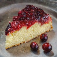Top angle photo of a piece of soft yellow cake that's topped in a fresh cranberry sauce on a metal plate. 3 fresh cranberries sit on the plate next to the cake.