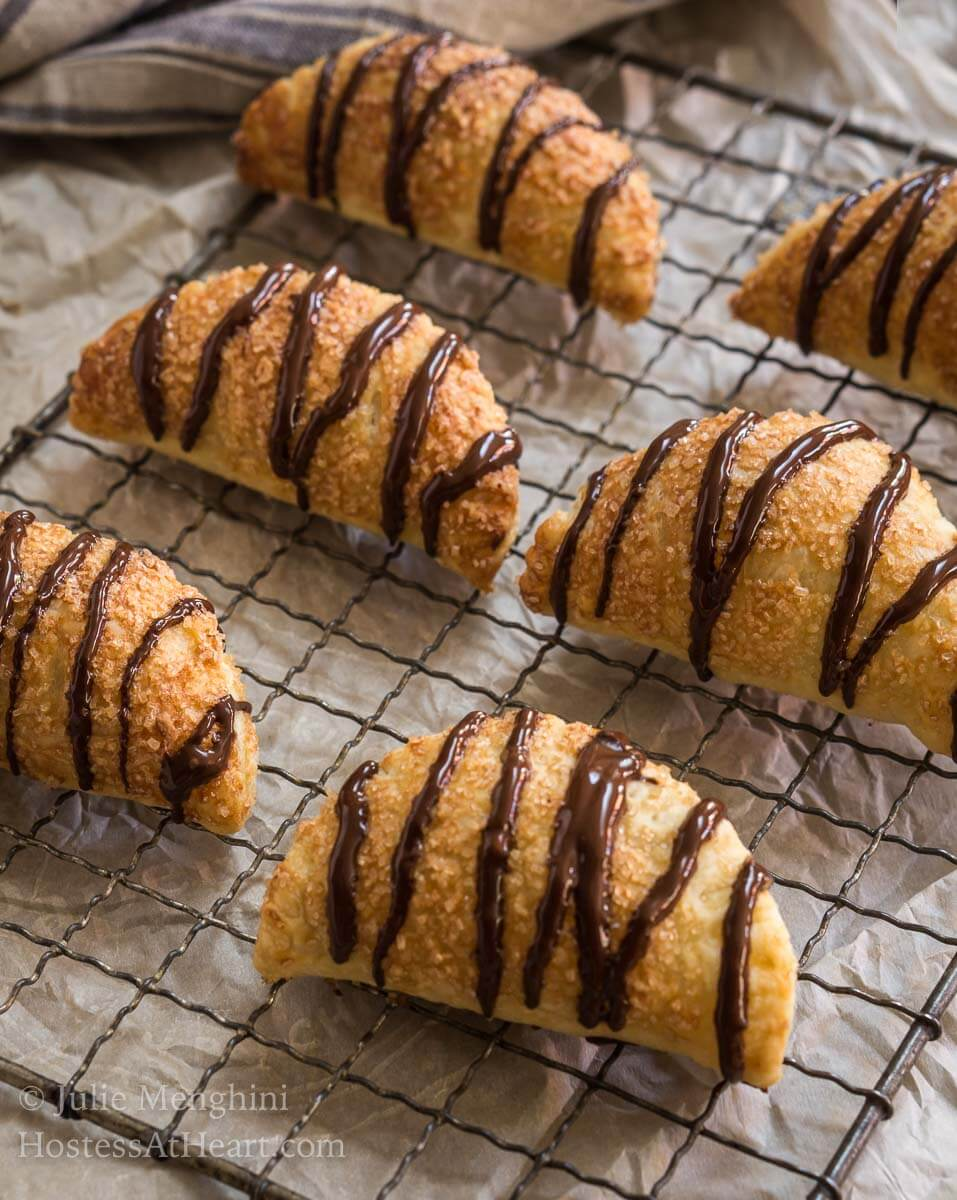 6 puff pastry crescents filled and drizzled with chocolate sit on a cooling rack over a piece of parchment paper.