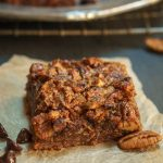 Side view of a Derby pie brownie bar topped with a baked pecan topping over a piece of parchment paper that's sprinkled with pecans. A tray of bars sits in the background over a cooling rack.