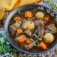 A bowl of food Vegetable Beef Soup full of carrots, potatoes, and chunks of beef in a dark gray bowl over a wooden placemat. Fresh herbs sit next to the bowl and a gold napkin sits in the background.