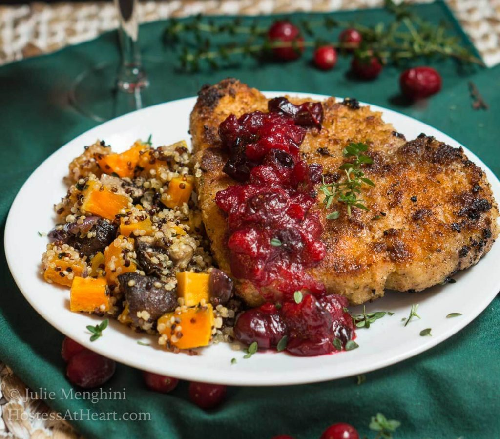 A white plate filled with a breaded Pork chop topped with a dollop of cranberry sauce and fresh thyme. Baked squash and quinoa sit next to the pork chop. The plate sits on a green napkin over a woven placemat. Fresh thyme and cranberries sit in the background.