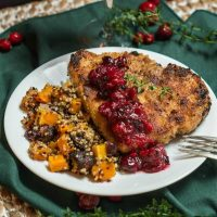 A white plate filled with a breaded Pork chop topped with a dollop of cranberry sauce and fresh thyme. Baked squash and quinoa sit next to the pork chop. The plate sits on a green napkin over a woven placemat.