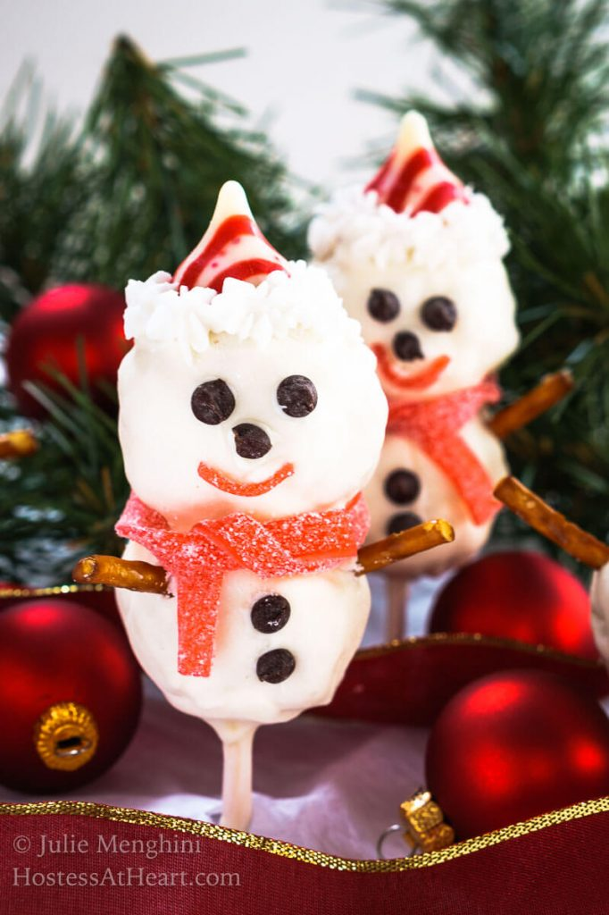 Two Rice Krispie Snowman Pops standing on their sticks with cute little chocolate chip eyes, striped candy hat and candy mufflers.