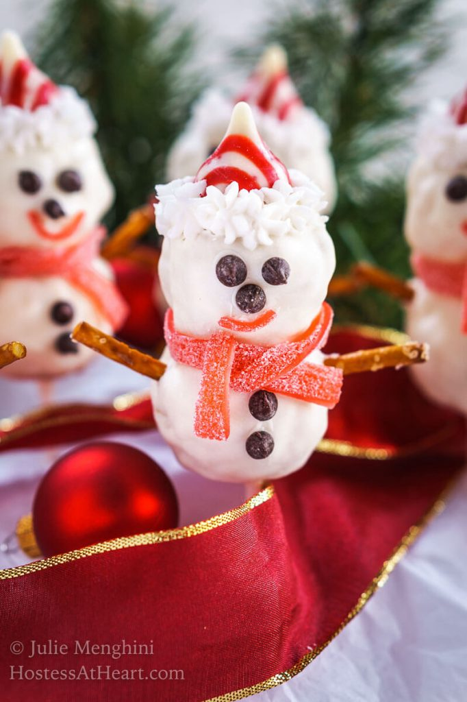 Close up view of a snowman pop with cute little chocolate chip eyes, striped candy hat and candy muffler and pretzel arms