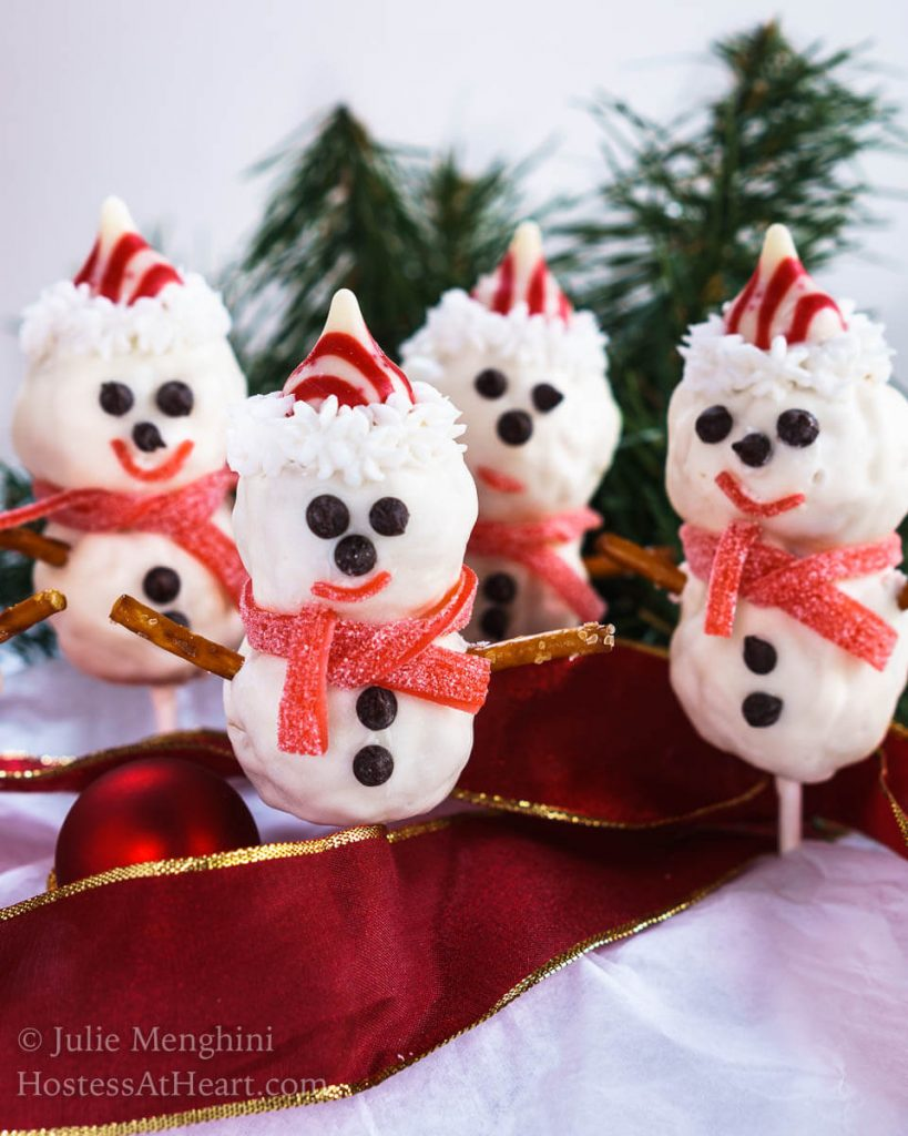 4 Rice Krispie Snowman Pops with cute little chocolate chip eyes, striped candy hat and a candy leather muffler