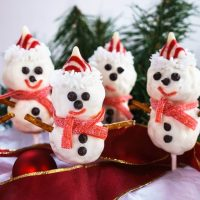 4 Rice Krispie Snowman Pops with cute little chocolate chip eyes, striped candy hat and a candy leather mufflers sit over a red ribbon with pine trees in the background.