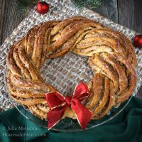 Sweet Nut Holiday Bread baked in the shape of a wreath and garnished with a red bow. A green napkin and a weaved placemat sit under the wreath. Two Christmas bulbs sit in the background.