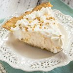 A slice of creamy angel food pie sitting in a buttery crust on a white plate.