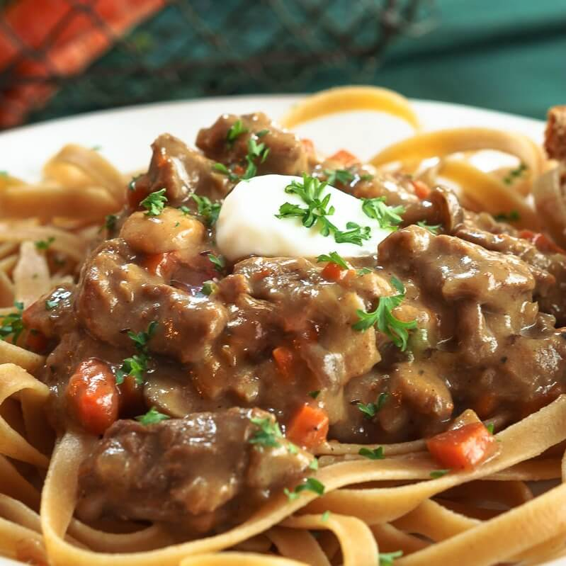 Close photo of beef stroganoff on a white plate with a spoonful of sour cream sitting on top of it.
