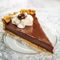 A slice of Dark Chocolate Pecan Tart with a piped star of whipped topping and a chocolate-dipped coffee bean sitting on a glass plate over a white tablecloth.