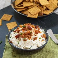 A bowl of Crab Dip with bacon sitting on a green napkin. A bowl of crackers sits in the background.