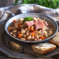 A bowl of Ham and bean soup garnished with big chunks of ham. Sliced bread and a spoon sits next to the bowl on a metal plate.