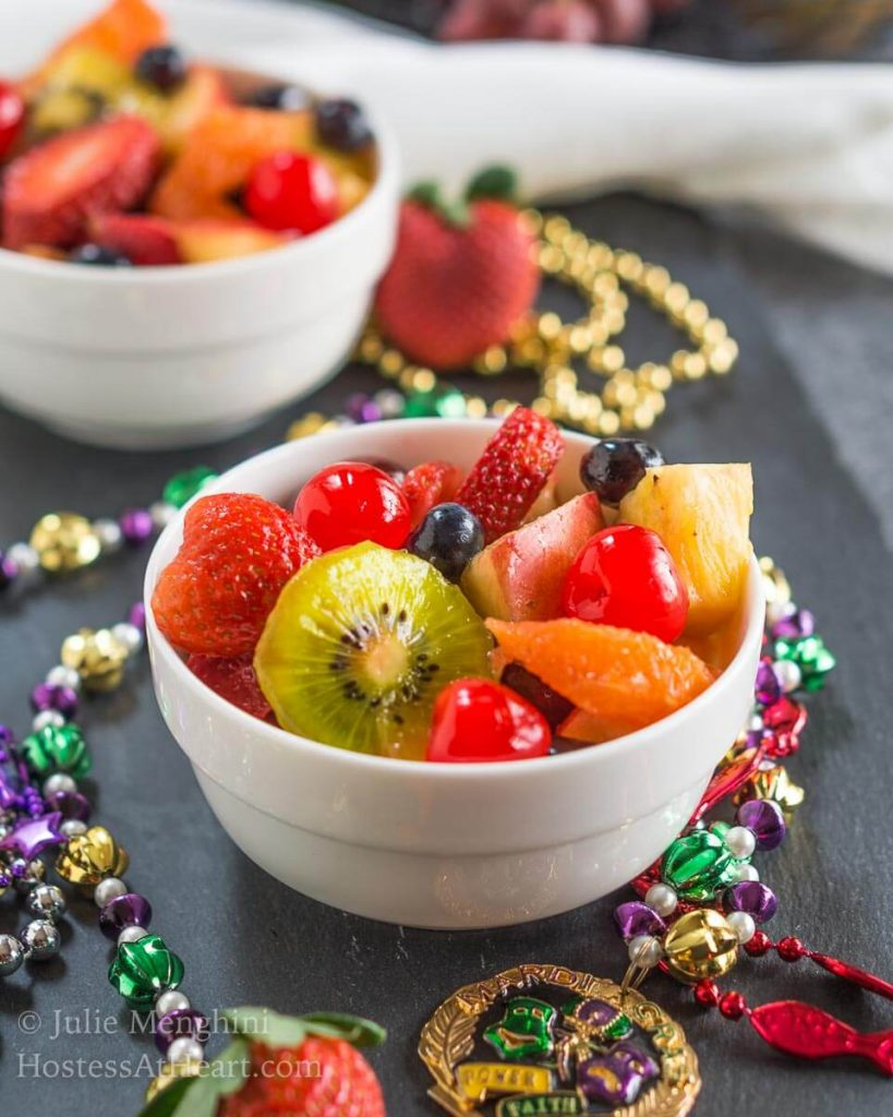 A two bowls fruit salad infused with Hurricane cocktail mix over gray slate and surrounded with Mardi Gras beads.