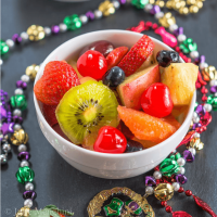 A bowl of Hurricane infused fresh fruit sitting on black slate and surrounded with Mardi Gras beads.