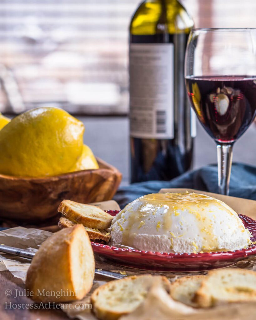 Side scene of homemade ricotta drizzled with honey sitting on a red plate in front of a bottle of a glass and bottle of red wine and fresh lemons.
