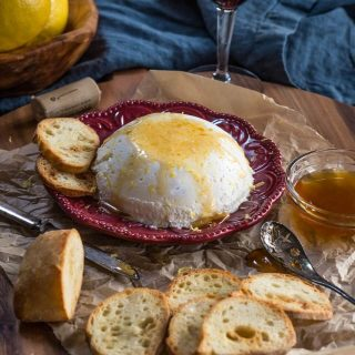 Red plate holds a bowl-shaped homemade ricotta drizzled with honey with slices of a baguette sitting in the front over a wooden cutting board.