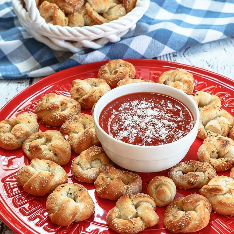 Red plate topped with baked pizza knots and a white bowl containing pizza sauce. A white basket of pizza rolls sit in the background over a blue checked napkin.