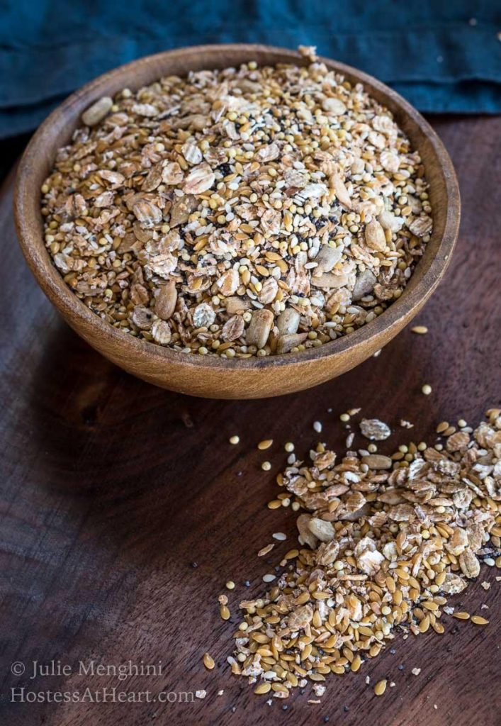 A wooden bowl filled with an Organic Whole Grain Bread Blend with some of the mix scattered on a wooden cutting board.