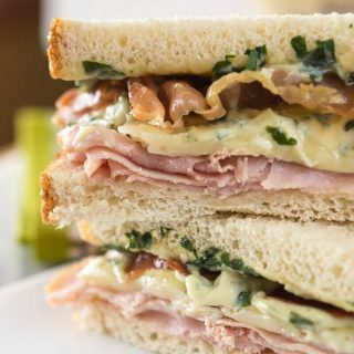 Table view of a sandwich filled with Ham, melted Brie, Prosciutto, and Basil Aioli.