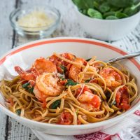 A white bowl filled with Shrimp Fettucine. A bowl of spinach and a bowl of parmesan sit in the background.