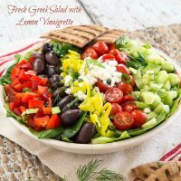 A white dish full of lettuce topped with red peppers, olives, banana peppers, tomatoes, cucumbers and garnished with cheese.