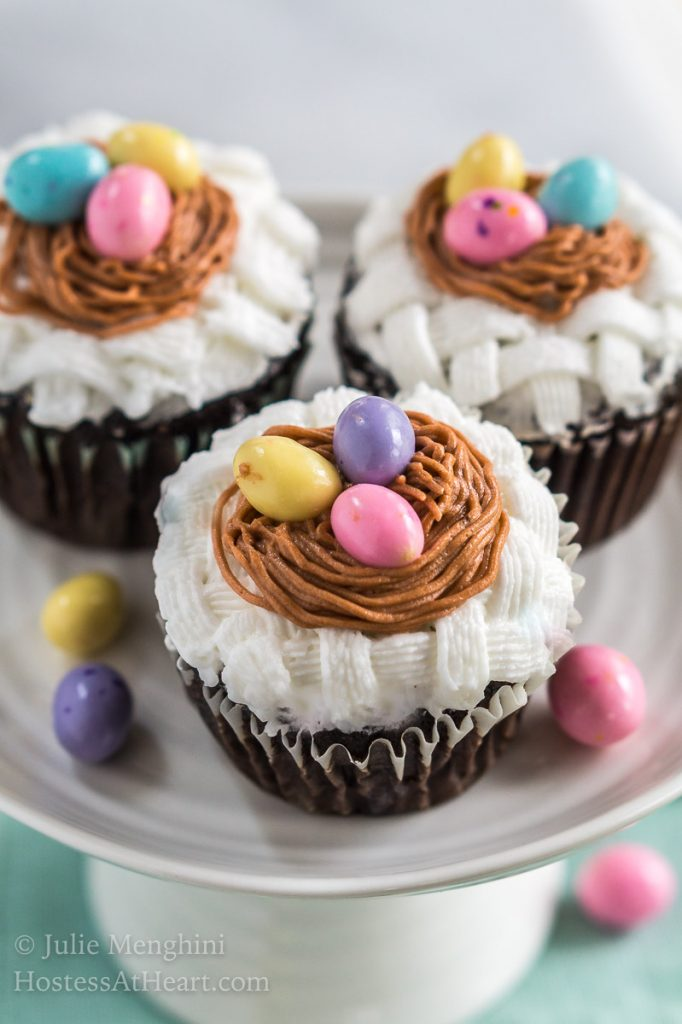Close up of hree cupcakes on a cake stand that are decorated with white basketweave under a piped birdnest and three candy eggs. The stand sits on a soft green napkin and additional candy eggs are sprinkled around the photo.