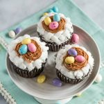 Three cupcakes on a cake stand that are decorated with white basketweave under a piped birdnest and three candy eggs. The stand sits on a soft green napkin and additional candy eggs are sprinkled around the photo.
