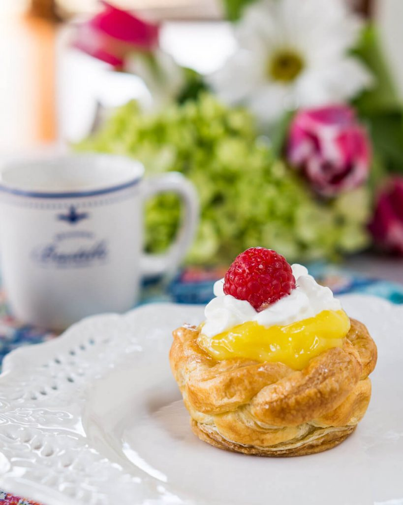A puff Pastry Basket filled with lemon curd on a white plate. A cup of coffee and a bouquet of flowers sits in the background.