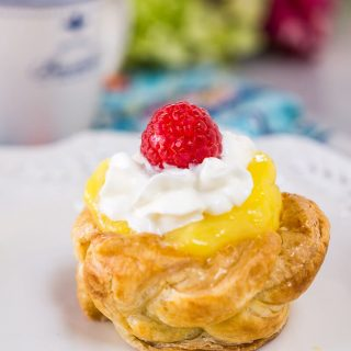 Puff Pastry Basket filled with a creamy tart lemon pudding and topped with whipped cream and a raspberry.