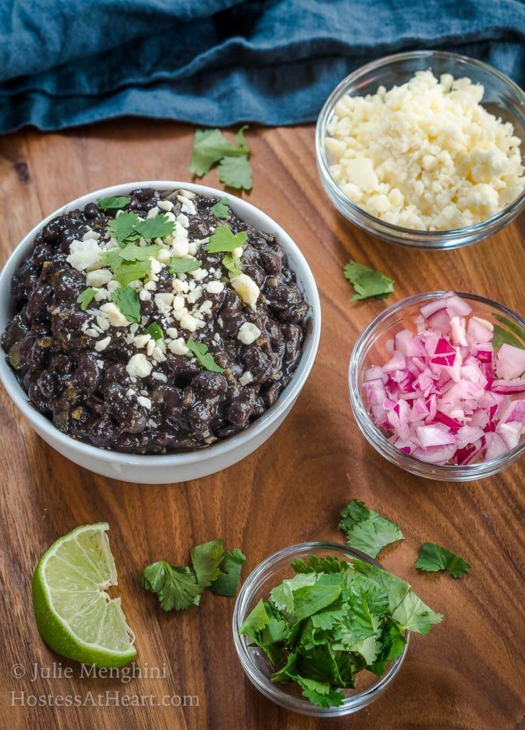 A bowl of black beans garnished with Cotija Cheese and cilantro. Dishes of cheese, red onion, and cilantro sit around the black beans with wedges of lime.