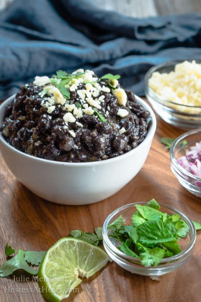 A white bowl filled with black beans garnished with cotija cheese and cilantro. Small dishes of cheese, onions, cilantro, and lime sit around the beans.