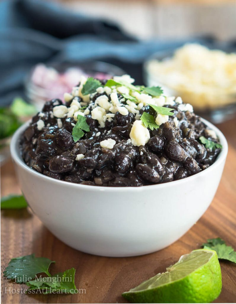 A bowl of black beans garnished with Cotija Cheese and cilantro. Dishes of cheese, red onion, and cilantro sit behind the black beans with wedges of lime.