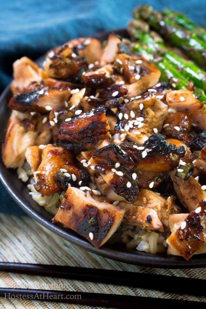 A side view of a gray plate holding diced chicken cooked in teriyaki sauce and sprinkled with sesame seeds sitting in front of grilled asparagus.
