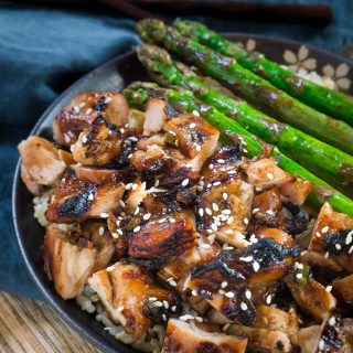 Top view of a bowl of diced chicken marinated and baked in a Teriyaki sauce over rice. Grilled asparagus sit next to the chicken. The bowl sits over a blue napkin.