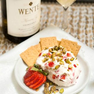 A goat cheese ball made with strawberries and pistachios sitting on a white plate with crackers on the side. A bottle of wine sits in the back.