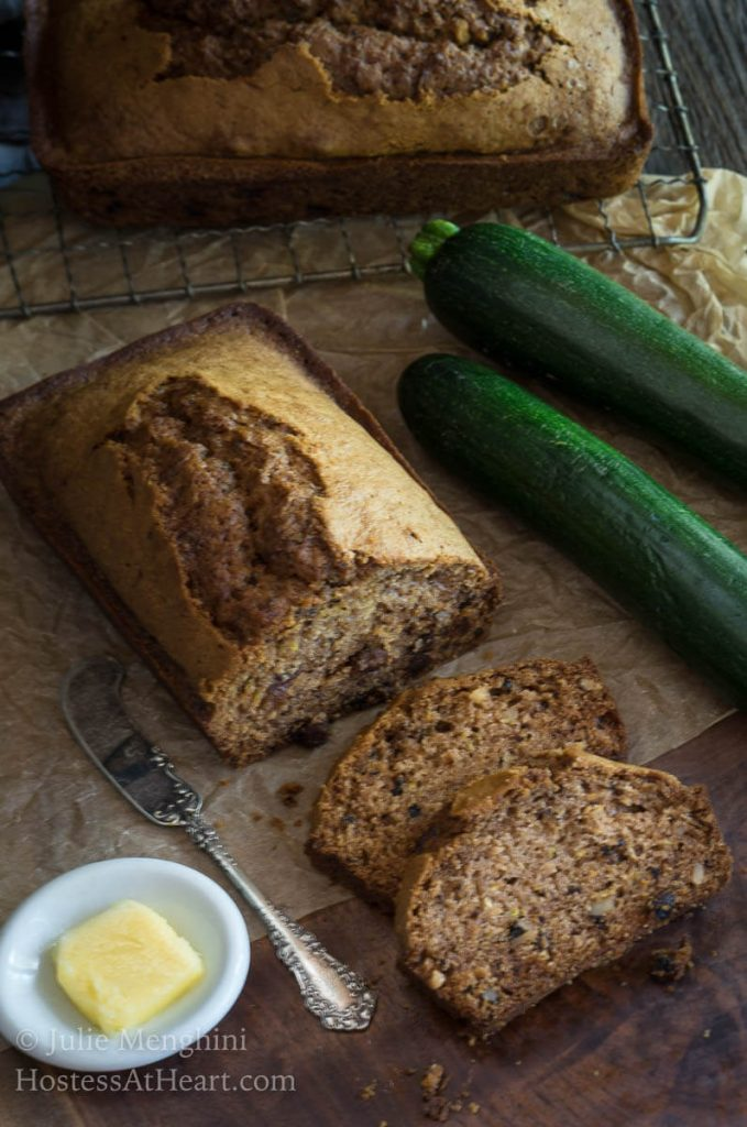 Top down view of a loaf of zucchini bread with the first to slices laying in front of it on a piece of parchment paper. A fresh zucchini sits to the back side and a white dish filled with butter sits to the front side.