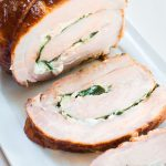 Top-angle view of a pork tenderloin that's been stuffed with goat cheese and spinach, tied and grilled over a white platter.