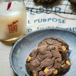 Three Chocolate Peanut Butter Chip cookies sitting on a blue enamelware plate. A jar of milk sits next to the plate and a cooling rack filled with cookies sits in the background.
