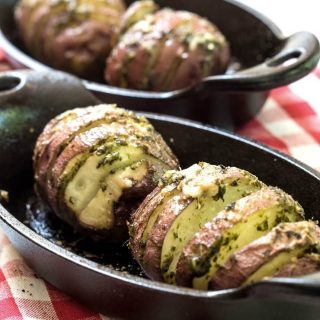 Two cast-iron casserole dishes holding red potatoes that have been sliced and loaded with garlic basil sauce over a red checked tablecloth.