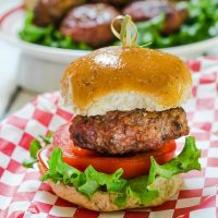 Side view of a hamburger that's been stuffed with Pepperjack cheese and pepperoncini sitting over a slice of tomato and lettuce between a bun. A skewer secures the bun to the burger. over a red checked cloth.