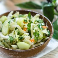 A wooden bowl heaped with Thai Basil Cabbage Slaw dotted with cucumbers and jalapenos.