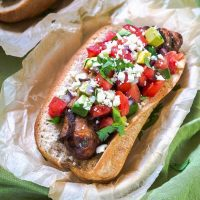 Top-down view of a Brat topped with Avocado Pico in a basket lined with parchment paper.