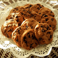 A lace-covered plate holding Oatmeal Chocolate Chip cookies.