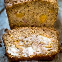 Front angle shot of a slice of peach bread shows cubes of yellow peaches and is covered in melted butter. The bread sits on a metal plate.