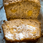 Top shot of a slice of peach bread shows cubes of yellow peaches and is covered in melted butter