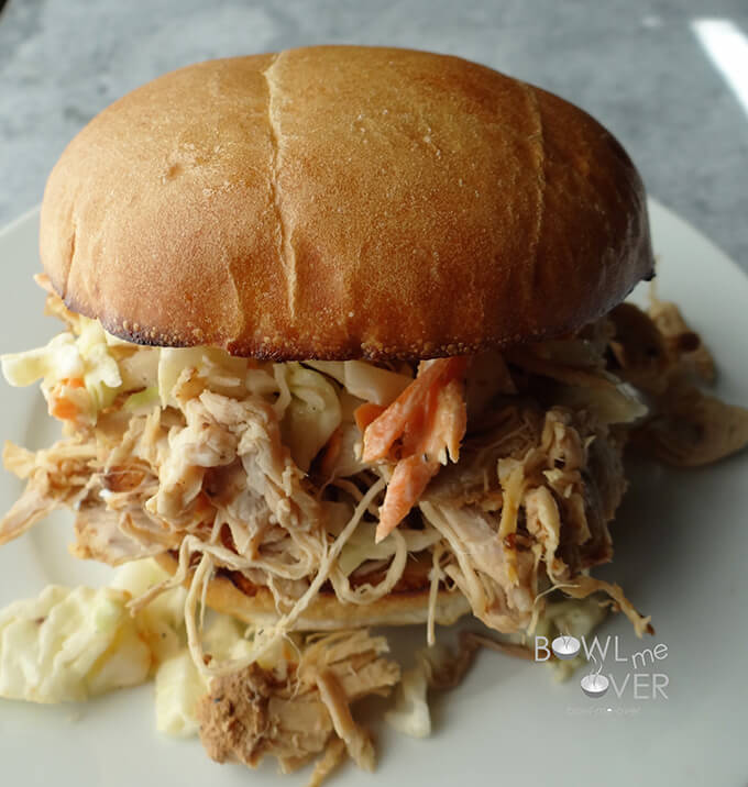 A close-up side view of a Kauai Pulled pork sandwich on a white plate, with Pulled pork spilling out of the bun.