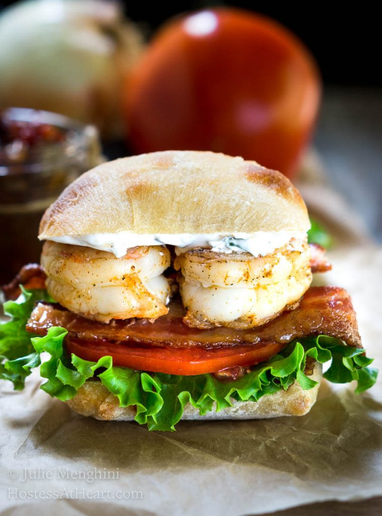 A closeup side view of a sandwich layered with spicy grilled shrimp, bacon, lettuce, tomato, and aioli inside a ciabatta roll. A jar of tomato relish sits in the background.